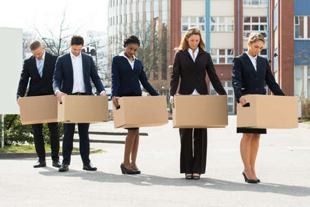 unemployed: Group Of Unemployed Businesspeople With Cardboard Boxes Standing In A Line Stock Photo