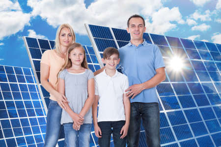 Portrait Of A Smiling Family Standing In Front Of Solar Panel photo