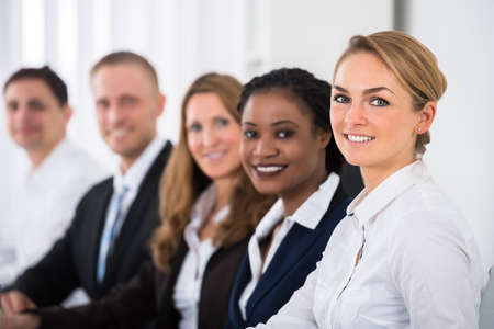 businesspeople: Happy Multiethnic Businesspeople Sitting In Row In Office Stock Photo