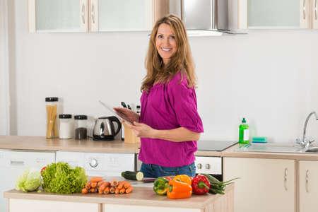 Gelukkig Holding Vrouw Digitale Tablet Cook in haar keuken