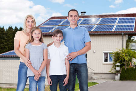 Portrait Of A Happy Family Standing Outside Their House With Solar Panels On Roof Standard-Bild