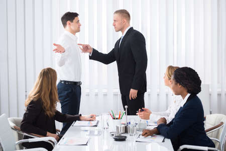Gruppo di uomini d'affari che cercano l'uomo d'affari che colpisce il suo collega nell'incontro
