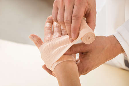 fracture arm: Close-up Of Doctor Hand Wrapping Elastic Bandage To Patient