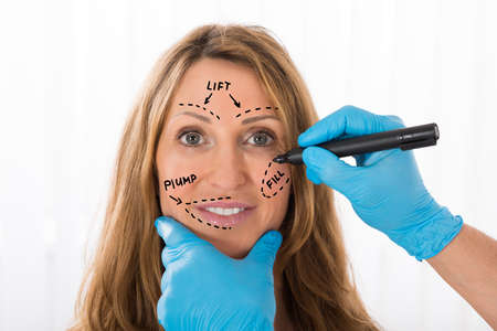 perforation: Close-up Of Happy Mature Woman With Perforation Lines Marked On Face