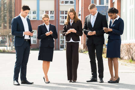 mobile phones: Group Of Multi-racial Businesspeople Using Mobile Phones;Outdoor