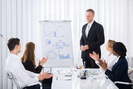 Groep zakenlieden klappen voor zakenman na presentatie