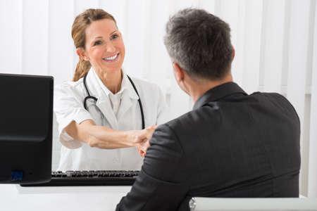 Glücklicher weiblicher Doktor Händeschütteln mit Geschäftsmann im Krankenhaus