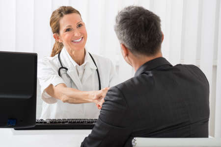 consultant physicians: Happy Female Doctor Shaking Hands With Businessman In Hospital Stock Photo