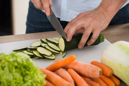 cucumber slice: Close-up Of Man Cutting Vegetable On Chopping Board In Kitchen