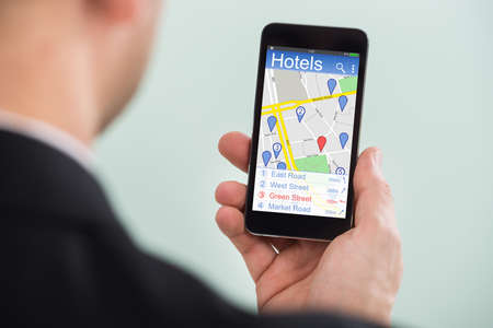 using phone: Close-up Of A Person Searching Hotels Using GPS Map With Navigation Pointers On His Smartphone