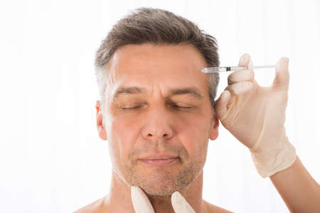 Close-up Of Mature Man Get Injection On His Face