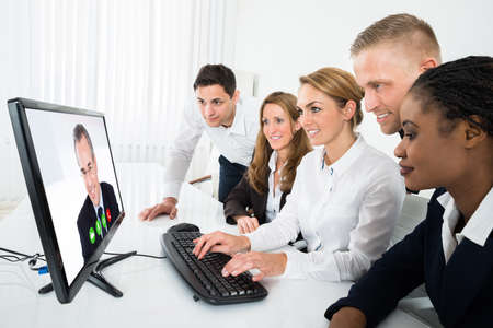 videoconferencing: Group Of Multiracial Businesspeople Videoconferencing On Computer In Office