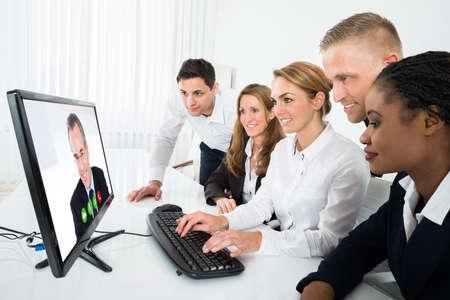 Grupo de videoconferencia empresarios multirraciales en el ordenador en la oficina