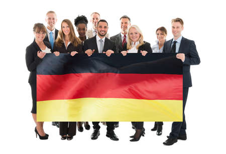 german: Businesspeople Holding German Flag Against White Background Stock Photo
