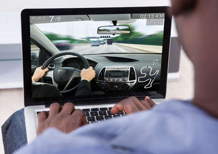 computer keyboard: Close-up Of Man Playing Car Game On His Laptop Stock Photo