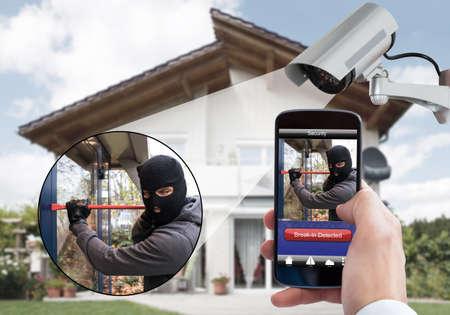 Persona mano que sostiene el teléfono móvil que detecta Burglar sistema de seguridad con cámaras de vigilancia del Detrás