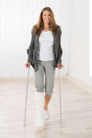 Happy Mature Woman With Fractured Leg Holding Crutches While Walking Stock Photo