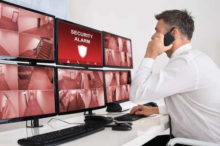 monitoreo: Operador de sexo masculino con walkie-talkie mientras supervisa múltiple CCTV Video