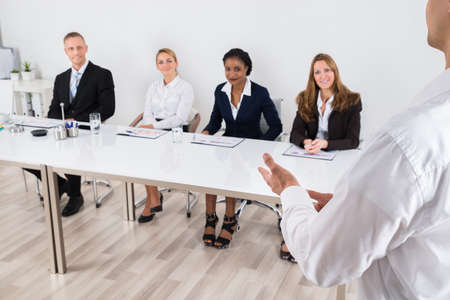 formulation: Businessperson Having Discussion With Colleague In Office Stock Photo
