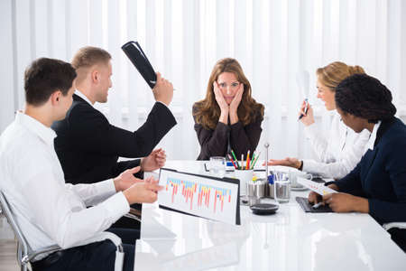 upset: Upset Businesswoman Sitting With Aggressive Colleague In Meeting
