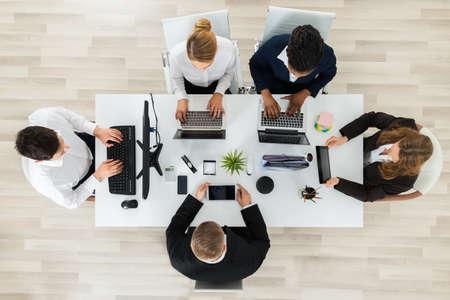Vista elevada de empresarios que trabajan en los ordenadores y portátiles en la oficina
