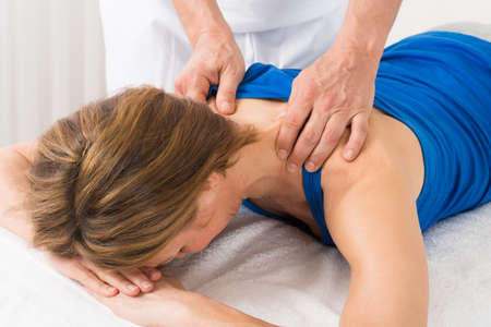 back rub: Close-up Of Person Giving Massage To Mature Woman Stock Photo