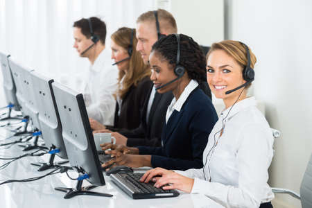headset woman: Call Center Operators In A Row Working On Computers In Office
