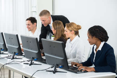 hilera: El hombre de negocios joven que ayuda a sus colegas en el trabajo de oficina