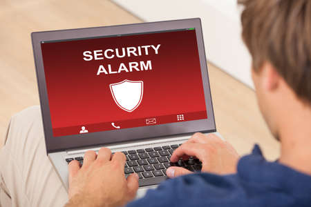 Close-up Of A Man Using Laptop Showing Security Alarm On Screen photo