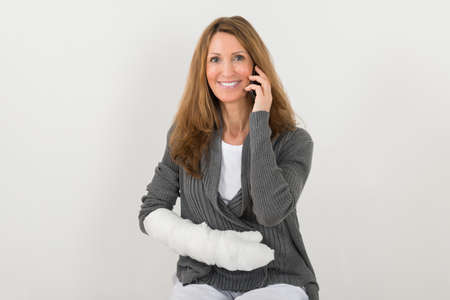 sprained joint: Mature Happy Woman With Broken Hand Talking On Mobile Phone Stock Photo