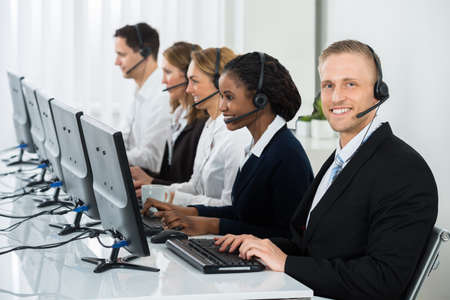 call centre girl: Team Of Businesspeople With Headsets Working In Call Center Office Stock Photo