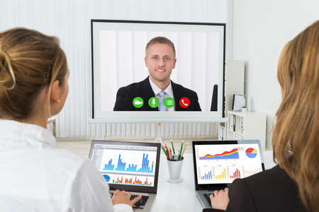 videoconferencing: Two Businesswomen With Graphs On Laptop Videoconferencing In Office