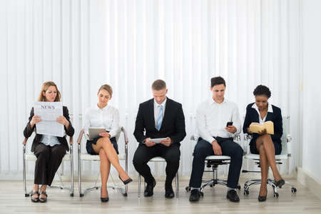 telephone interview: Group Of Businesspeople Doing Various Activities While Waiting For Interview