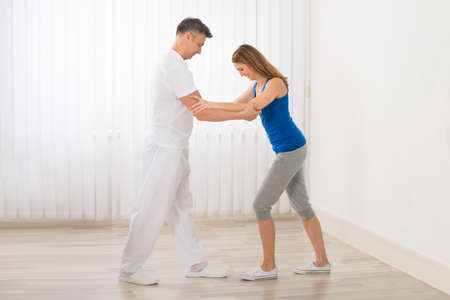 arm muscles: Physiotherapist Assisting Happy Mature Woman For Exercising