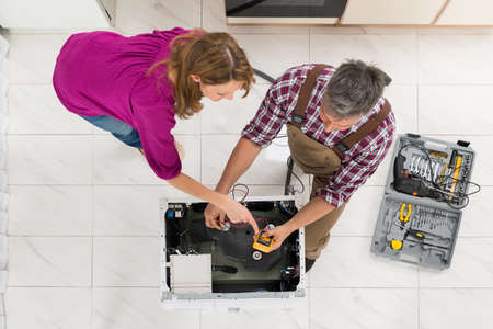 multimeter: High Angle View Of Woman Looking At Technician Checking Washing Machine With Digital Multimeter