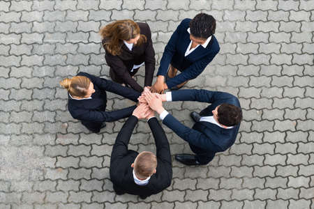 high angle: High Angle View Of Businesspeople Stacking Hands