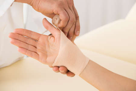 sprained joint: Close-up Of Doctor Hand Wrapping Elastic Bandage To Patient