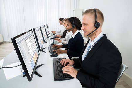 centre: Team Of Businesspeople With Headsets Working In Call Center Office Stock Photo