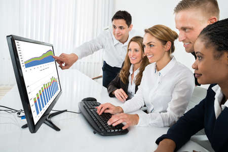 pc screen: Group Of Multiracial Businesspeople Looking At Graph On Computer In Office