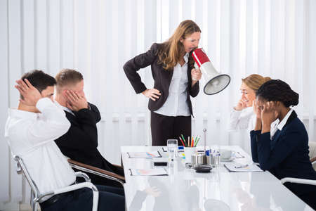 dominant woman: Unhappy Businesswoman Shouting Through Megaphone On Businesspeople In Office Stock Photo