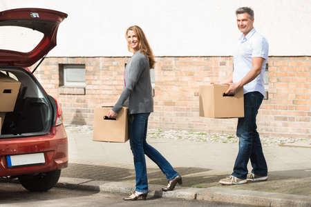 tronco: Feliz maduro pares que lleva la caja para poner en el coche Foto de archivo