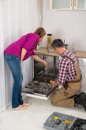 dishwasher: Woman Looking At Male Repairman Checking Dishwasher With Digital Multimeter Stock Photo