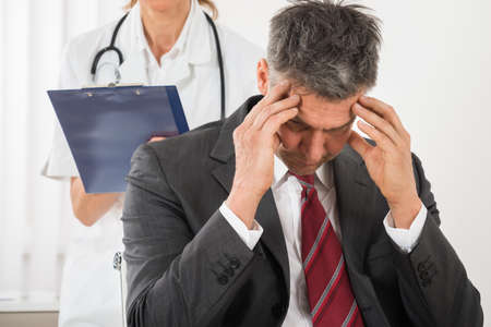 clinical psychology: Doctor With Clipboard Standing Behind The Businessman Having Headache In Clinic Stock Photo