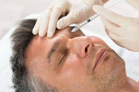 Älterer Mann empfangen Kosmetische Einspritzung mit Spritze in der Klinik Lizenzfreie Bilder