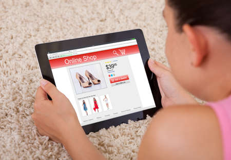 Close-up Of A Woman Shopping Online With Her Digital Tablet At Home photo