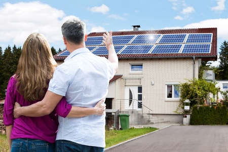front house: Rear View Of Couple Standing In Front Of Their House Stock Photo