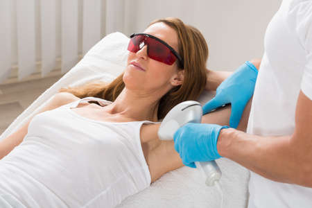 underarm: Mature Woman Receiving Underarm Laser Hair Removal Treatment