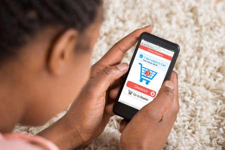 mujeres africanas: Primer plano de la mujer compras en línea con la aplicación en su teléfono móvil