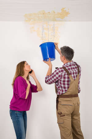 drop ceiling: Worker Collecting Water In Bucket From Ceiling While Woman Talking On Mobile Phone