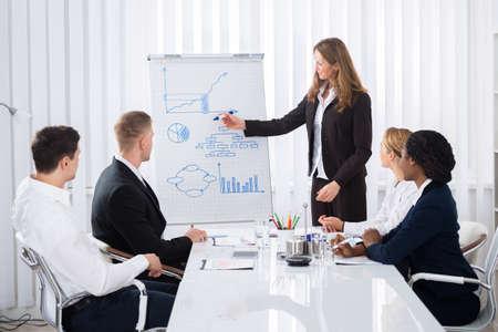 Groep Zakenlui die Zekere Onderneemster bekijken die in Presentatie verklaart Stockfoto